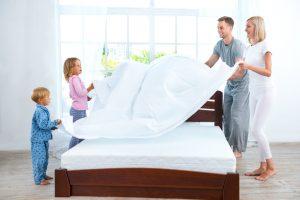 familia poniendo sábanas a un colchon