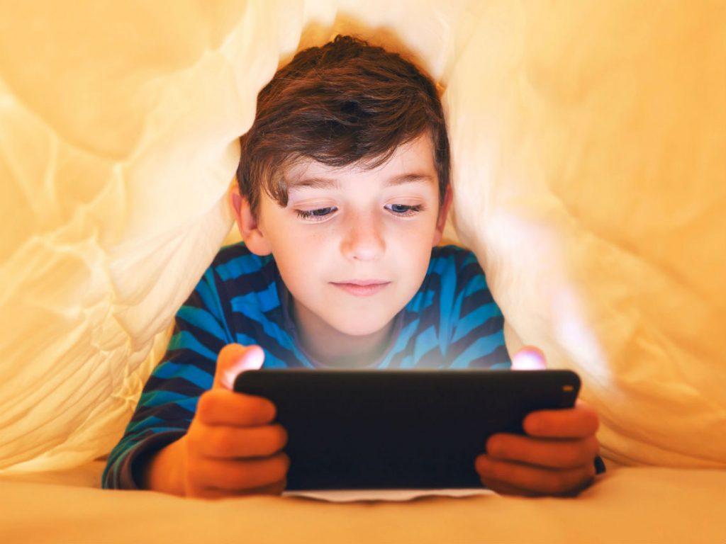 niño usando celular en la cama